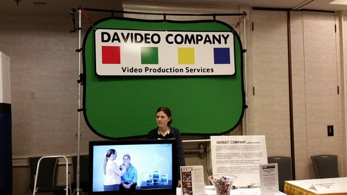 Lead Editor and Creative Director, Candice Moore, standing at the Davideo Company Booth at a trade show