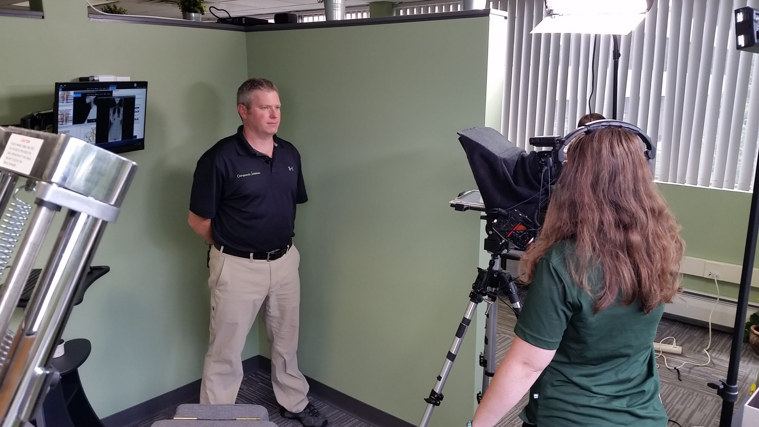 Lead Editor and Creative Director, Candice Moore, using a teleprompter while recording a video with Dr. Chris Hauck of Chiropractic Solutions